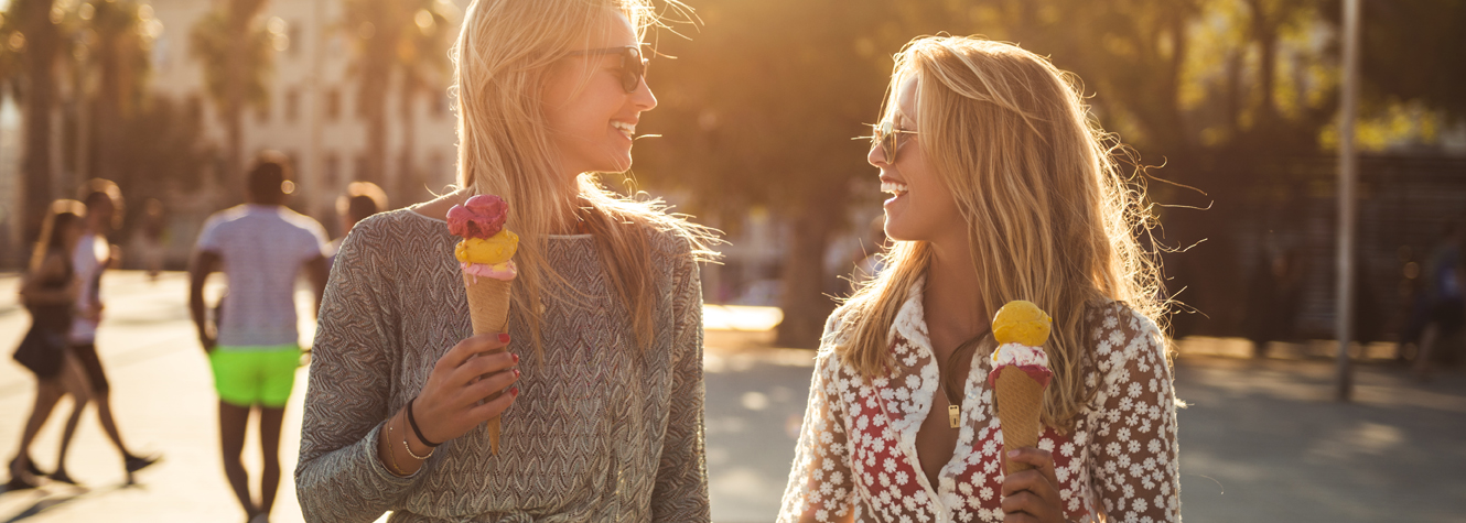 Two young women walk along a sunny street with ice cream in hand.