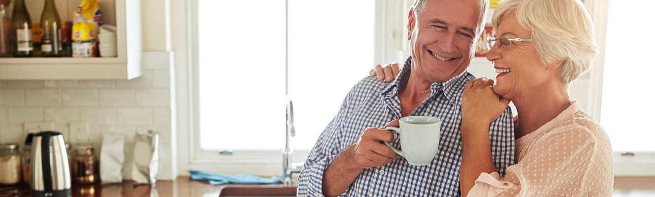 An elderly couple smiles as they hug in their kitchen and enjoy coffee.