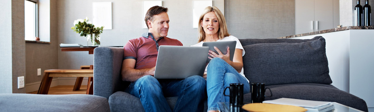 Couple on laptop sitting in a living room.