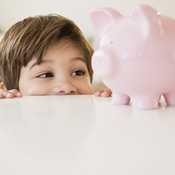 A young boy peering at a piggy bank