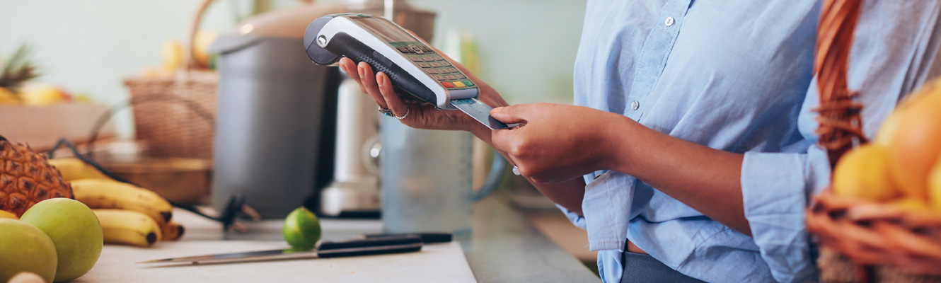 A woman in a juice shop swipes a credit card for a customer to complete a transaction.