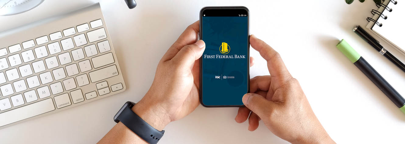 A pair of hands hold a cell phone with the First Federal Bank mobile app showing.